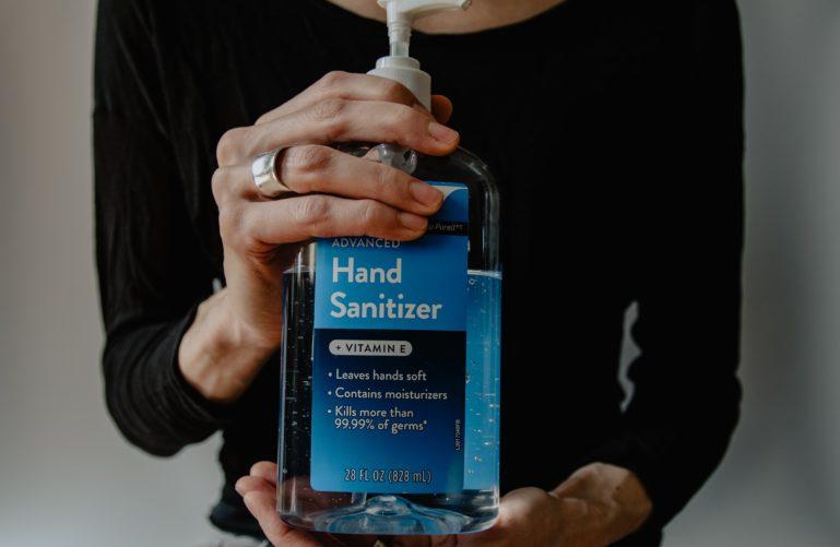 Personne tenant un flacon de gel  hydroalcoolique dans les mains pour assurer la désinfection et la lutte contre le coronavirus